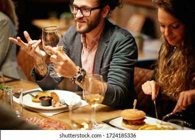 Hipster sitting with his friends at restaurant for diner, drinking wine and chatting.