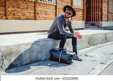 Hipster sitting and waiting seriously with bag on the floor