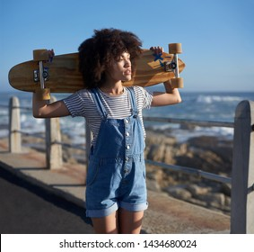 hipster skater woman with longboard and afro on sunny day by the ocean