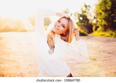 Hipster smiling girl standing outdoors on a sunny summer day. Vintage color