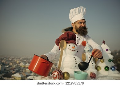 Hipster smiling with ladle in white uniform. Cooking and diet concept. Cook, snowmen and snow xmas tree on blue sky. Christmas and new year holidays food. Man in chef hat ladling soup on winter day.