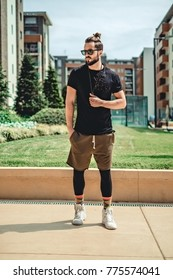 Hipster in sportswear standing  seriously in the street