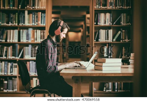 Hipster-Studierende, der an der Universität Bibliotheksstudium absolviert hat