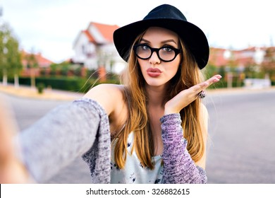 Hipster stunning woman making selfie , sending kiss, surprised funny emotions, natural make up, long blonde hairs, hipster hat and glasses, amity time, countryside.