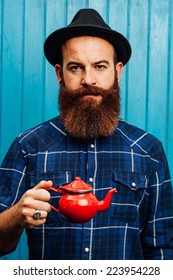 Hipster style bearded man with a red teapot