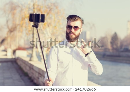 Hipster style bearded man taking selfie with selfie stick.