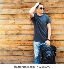 Hipster style. handsome young man with a fashionable hairdo. vintage photo. The guy standing near the old wooden wall. In the hands of a fashion backpack and a lion, sunglasses, sneakers, jeans