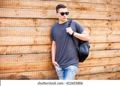 Hipster style. handsome young man with glasses and a fashionable hairdo. vintage photo. The guy standing near the old wooden wall. In the hands of a fashion backpack and a lion, sunglasses