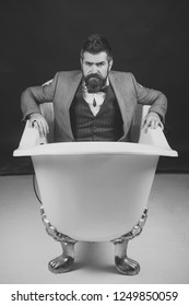 Hipster with stylish appearance in luxury old fashioned bathtub. Man or seller of sanitary ware on dark background. Guy with strict face in suit sits in bathtub. High quality sanitary ware concept.