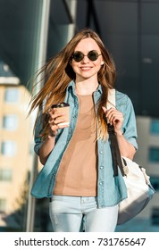 Hipster stylish girl wear sunglasses walk and hold cup of coffee