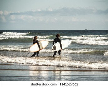 hipster surfer couple with surfboards walking in the ocean by sunset