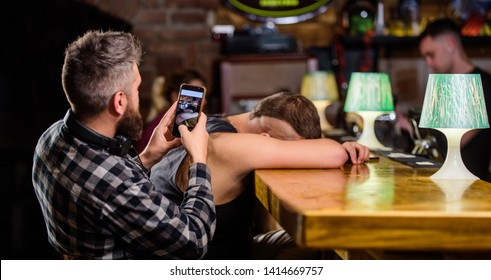 Hipster taking photo drunk friend. Drunk friends in bar. Fall asleep at bar counter. Take photo to remember party. Hipster making fun of drunk friend. Man drunk fall asleep and guy with smartphone.