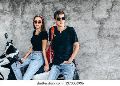 Hipster teen girl and boy wearing blank black t-shirt, jeans, headband and glasses sitting on motorbike against gray street wall. Same clothes look for teenage friends.
