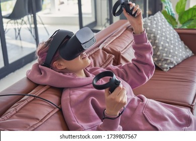Hipster teen girl pink hair wear vr glasses headset hold controllers play video game simulator enjoy immersive futuristic virtual reality 3D vr travel tour, watch 360 video, shopping on sofa at home.