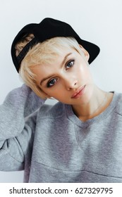 Hipster teen girl posing over wall. Street swag style, cap, natural short hair, beauty model face