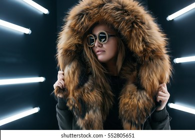 Hipster teen girl in sunglasses posing over wall,wearing warm casual fur coat,autumn style,happy and positive girl,glam rock style,natural long hair,hipster girl,swag style,beauty model face