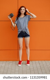 Hipster teen with vintage photo camera in one hand standing in front of orange wall, copy space, vintage toned image