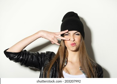 Hipster teenage girl with beanie hat and leather jacket posing making confident facial expression showing two fingers against white wall background. Modern young people.