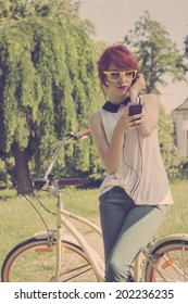 Hipster teenage girl on her vintage bike, listening to the music on her purple smart phone. Retro colors, toned image