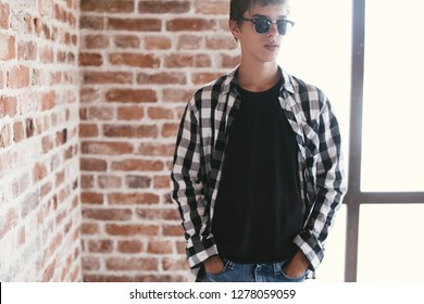 Hipster teenage guy wearing blank black tshirt and gingham shirt and fashion sunglasses posing against brick wall.