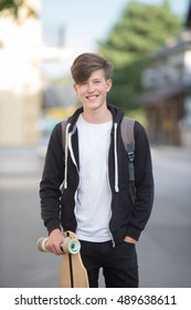 Hipster teenager holding longboard in a suburban street.