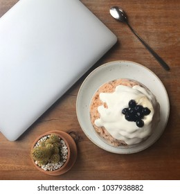 Hipster teenager snap a picture before eat Thai tea Kakigori (ice flake) topping with bubble with notebook and cactus on the wood table. Social Media trend concept.