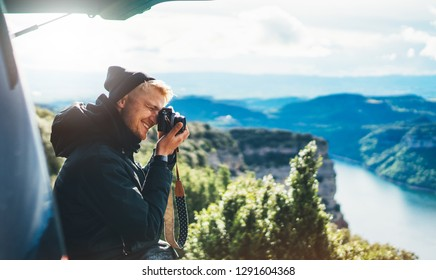 hipster tourist hold in hands taking photography click on retro vintage photo camera in auto, photographer looking on camera technology, panoramic landscape vacation concept, sun flare mountain