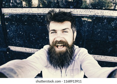 Hipster, tourist with tousled hair and long beard looking at camera, taking selfie photo. Vlogging concept. Man, tourist with beard and mustache on cheerful, smiling face, black marble background.