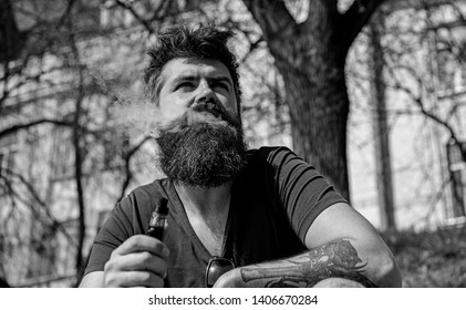 Hipster with tousled hair and gray on relaxed dreamy face with white smoke flying out of mouth. Vaping and habits concept. Man with beard and mustache smoking, urban background.