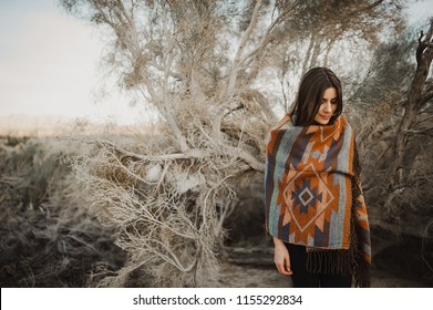 Hipster traveler girl in gypsy look in desert nature, lookijg down.  Artistic photo of young hipster traveler girl in gypsy look, in Coachella Valley in a desert valley in Southern California.