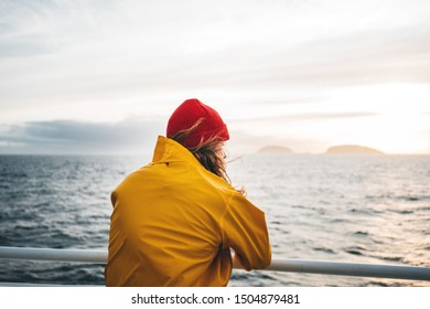 Hipster traveler wearing red hat and yellow raincoat looking away at cloudy mountain and sunset sea. Alone man traveling  at scandinavian authentic ocean landscape by ship