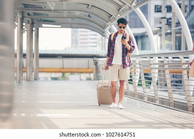 hipster traveller young man with backpack looking at smarphone