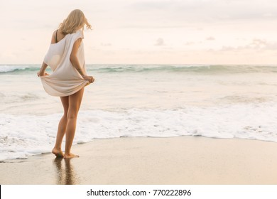 Hipster trendy girl hold her long summer dress and bikini trying not to wet it in waves. Sporty fit lady on sea sand beach sunset or ocean sunrise. Travel, active, yoga, freedom lifestyle concept.