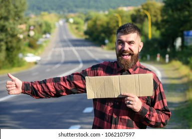 Hipster try to stop car with cardboard sign and thumb up gesture, copy space. Man with cheerful face and beard travelling by hitchhiking with road on background. Travelling and hitchhiking concept.
