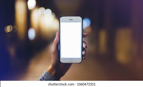 hipster using in hands clean gadget mobile phone closeup, blogger pointing finger on blank screen smartphone on background bokeh light in night city, mockup street, online wifi internet concept