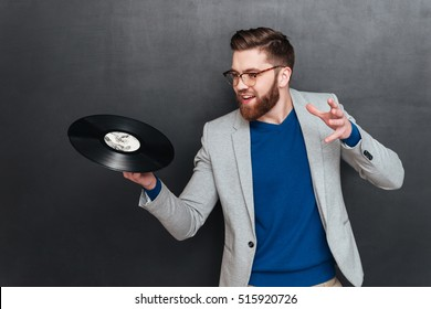 Hipster with vynil. in studio. laking at vynil. isolated black background