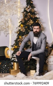 The hipster waiting for a Christmas party. Pensive man with a beard in a gray jacket with a bow-tie in the handsel of the Christmas holidays. Bearded elegant man in a suit at New year's eve.