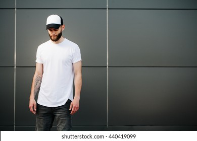 Hipster wearing white blank t-shirt and a baseball cap with space for your logo