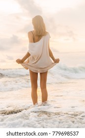 Hipster woman after hot summer day hold her long light dress trying not to wet it in cool water. Fit lady in sand sea beach sunset or ocean sunrise. Travel, active, yoga, freedom lifestyle concept.