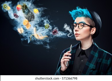 hipster woman with blue hair smoking fruit electronic cigarette on black background. Vape advertisement concept. Copy space