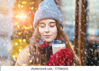 Hipster woman with closed eyes in warm clothes, red mittens with disposable cup of coffee outdoor in city street. Snowfall and sun glare effect. Wonder emotion fairytale and christmas concept.