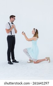 Hipster woman doing a marriage proposal to her boyfriend on white background