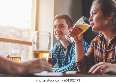 Hipster woman drinking beer with friends at bar or pub