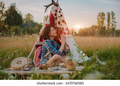 hipster woman in the form of a Shaman is looking for inspiration from the dream catcher in a wigwam in nature. Prayer, fantasy, sunset