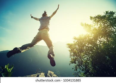 hipster woman hiker jumping on cliff's edge