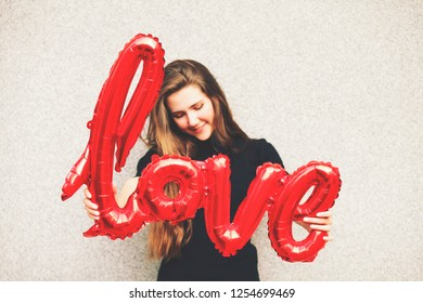 Hipster Woman holding a red balloon with a LOVE shape word. Lifestyle outdoors, toned instagram filters