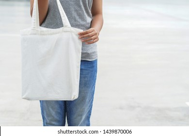 hipster woman holding white tote bag for mock up blank template