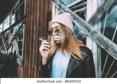 Hipster woman smoking a sigarette, wearing a hat and vintage, hipster glasses. A lot of smoke. Soft lights. Trendy street style.