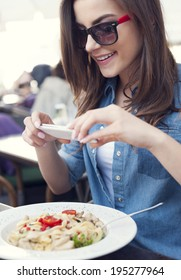 Hipster woman taking a picture of italian meal