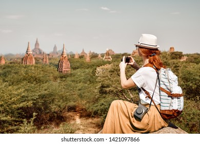 Hipster woman traveler with backpack enjoying views of Buddhist stupas in the ancient Bagan. Myanmar.